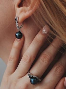Verticale close-up die van een vrouw is ontsproten die een ring en oorringen met een zwarte hanger draagt