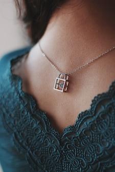 Verticale close-up die van een vrouw is ontsproten die een zilveren halsband met een mooie slothanger draagt