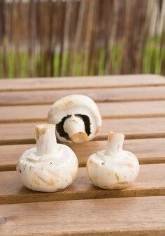 Verticale close-up shot van drie verse champignons op een houten oppervlak