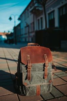 Verticale close-up shot van een grijze en bruine rugzak op de grond in de straat