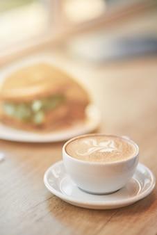Verticale close-up shot van een kopje koffie cappuccino en sandwich op houten tafel in café