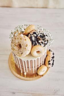 Verticale close-up shot van heerlijke donut choco verjaardagstaart met donuts bovenop en witte drip