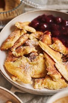 Verticale close-up shot van heerlijke donzige pannenkoeken met kersen en poedersuiker