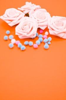 Verticale close-up shot van roze rozen en pompons geïsoleerd op een oranje achtergrond met kopie ruimte