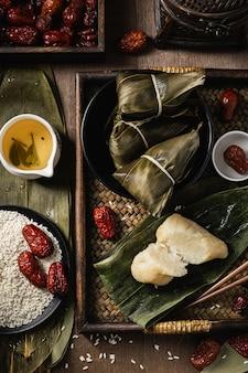 Verticale close-up shot van voorbereiding van rijst dumplings met bananenbladeren