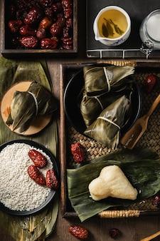 Verticale close-up shot van voorbereiding van rijstbollen met bananenbladeren
