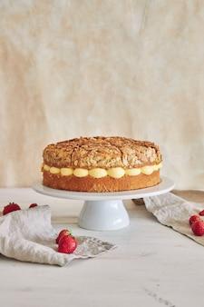 Verticale close-up van de heerlijke vanilleroomtaart met aardbeien erin op een witte tafel