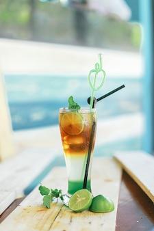 Verticale close-up van een heerlijke koude cocktail op tafel met limoenen (lemmetjes) onder de lichten