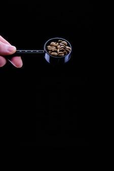 Verticale close-up van een persoon die een lepel met koffiebonen houdt die op zwarte worden geïsoleerd