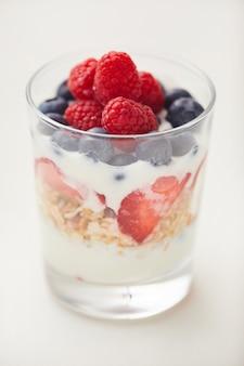 Verticale close-up van heerlijke yoghurt parfait cup met verse bessen en muesli geïsoleerd
