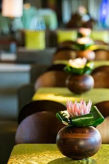 Verticale close-up van lotusbloemen in een vaas op tafel