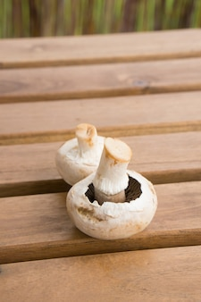 Verticale close-up van twee verse champignons op een houten tafel oppervlak