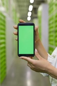 Verticale close-up van vrouwelijke handen met smartphone met groen scherm tegen self storage faciliteit oppervlak