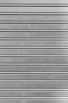 Verticale compositie van een grijs metalen gordijn dat een gesloten winkel of huis beschermt