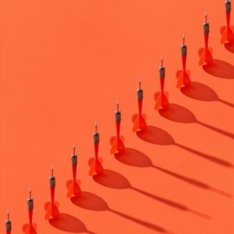 Verticale darts in een diagonale lijn met schaduwen op een oranje achtergrond, kopieer ruimte.