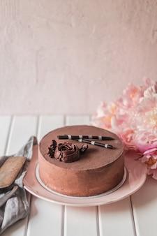 Verticale esthetische opname van een smakelijke chocoladetaart met een roos