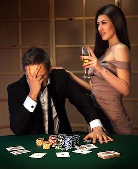 Verticale foto gefrustreerde man en vrolijk meisje met een glas champagne die samen poker spelen. afhankelijk van het concept van gokken en casino's