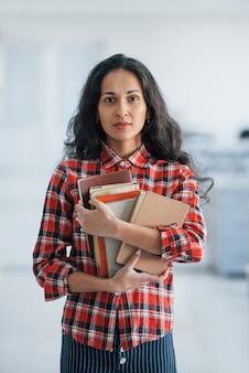 Verticale foto van aantrekkelijke jonge vrouw die zich in het bureau bevindt en boeken en documenten houdt