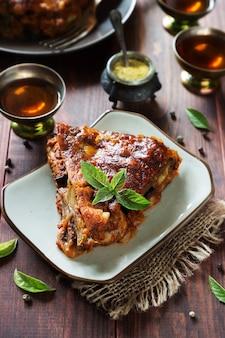 Verticale foto van aubergine-lasagne met kaas, vlees, tomatensaus en basilicum