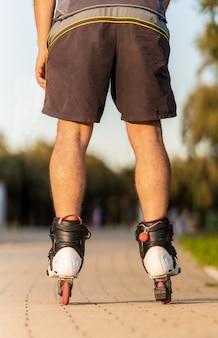 Verticale foto van de benen van een man die schaatst met inline skates
