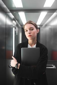 Verticale foto van de jonge kalme laptop van de onderneemsterholding in haar handen