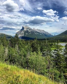 Verticale foto van de mount rundle omgeven door groen onder een bewolkte hemel in canada