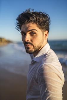 Verticale foto van een brunette man in een wit overhemd tegen een oceaan