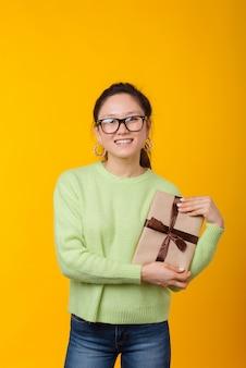 Verticale foto van een glimlachende vrouw die een verpakt boek als een geschenk