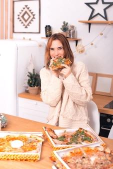 Verticale foto van een jong meisje dat pizza eet en bij de camera in haar keuken glimlacht
