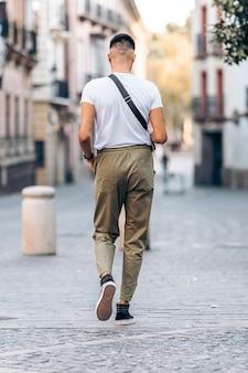 Verticale foto van een jonge blanke man die in vrijetijdskleding over straat loopt