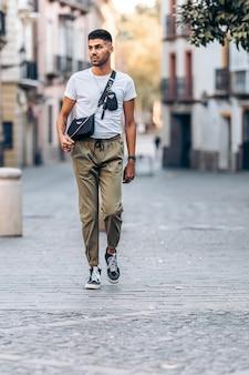 Verticale foto van een jonge man die afgeleid door de straat loopt, gekleed in vrijetijdskleding