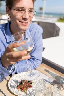 Verticale foto van een jonge man met piercings en glazen met een glas witte wijn in zijn hand en een bord met salade en zalm met de tafel van een restaurant