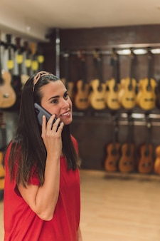 Verticale foto van een jonge vrouw die praat met de mobiel in een instrumentenwinkel