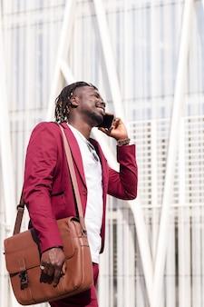Verticale foto van een lachende zwarte zakenman met aktetas loopt door het financiële centrum van de stad pratend over telefoon, concept van technologie en communicatie, kopieer ruimte voor tekst