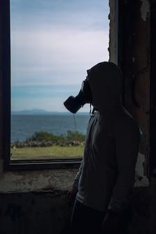 Verticale foto van een man met een gasmasker voor een raam in een verlaten gebouw
