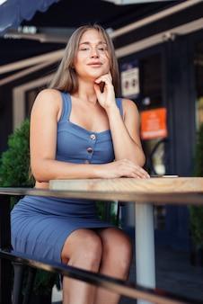 Verticale foto van een meisje in een café. een meisje in een blauwe top zit zijwaarts.