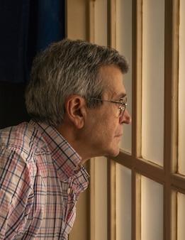 Verticale foto van een oude man met een bril die door het raam kijkt