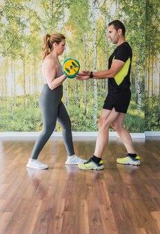 Verticale foto van een personal trainer die een vrouw helpt om gewichten te doen in een sportschool met een muur versierd met natuurlijke elementen.