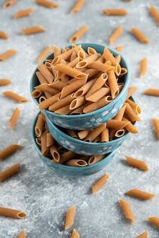 Verticale foto van een stapel kommen vol met bruine penne pasta over grijs oppervlak.