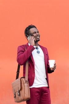 Verticale foto van een stijlvolle zwarte zakenman gekleed in pak met aktetas en koffie praat op slimme telefoon voor rode achtergrond, kopieer ruimte voor tekst, concept van technologie en communicatie