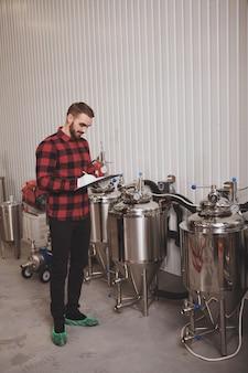 Verticale foto van een volledige lengte van een brouwer die op zijn klembord schrijft terwijl hij in zijn microbrouwerij werkt
