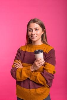 Verticale foto van een vrouw die naar de camera lacht terwijl ze een koffiekopje vasthoudt.