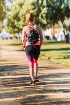 Verticale foto van een vrouw in sportkleding die over straat loopt met een zwarte rugzak.