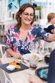 Verticale foto van een vrouw met een gebloemde jurk in een tafel van een restaurant met een gerecht van gebakken kip geserveerd in een donker bord met een kleine vierkante kom yoghurt