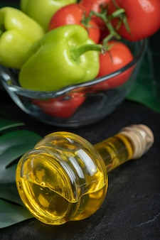 Verticale foto van fles olijfolie voor verse groenten.