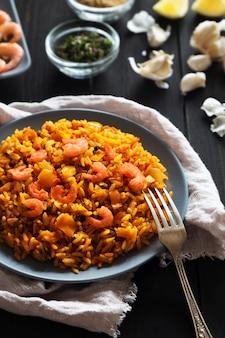 Verticale foto van gebakken rijst met garnalen, citroen en groenten op grijze plaat en linnen