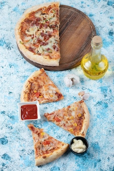 Verticale foto van gesneden pizza met sauzen.