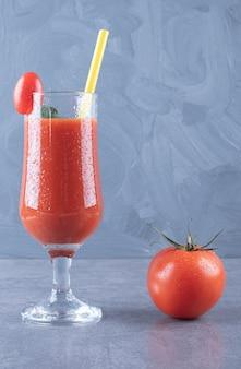 Verticale foto van glas vers tomatensap en tomaat op een grijze achtergrond.