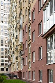Verticale foto van hoge nieuw gebouwde moderne herenhuisvoorgevel, gras op grond