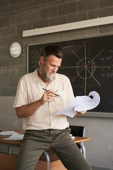 Verticale foto van mannelijke leraar van middelbare leeftijd met baard corrigeert examens in de klas